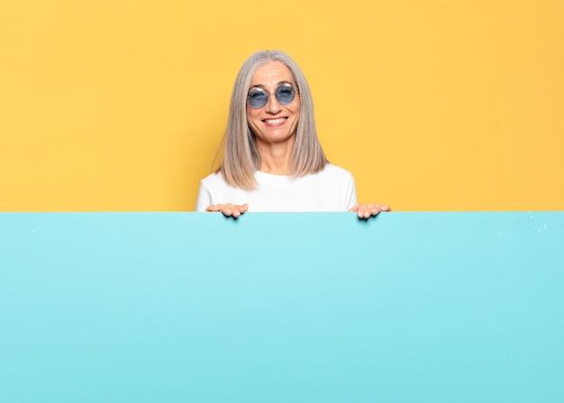 Starsza ładna kobieta w okularach przeciwsłonecznych kopiuje koncepcję przestrzeni