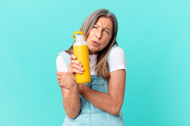 Starsza ładna kobieta z kawowym termosem