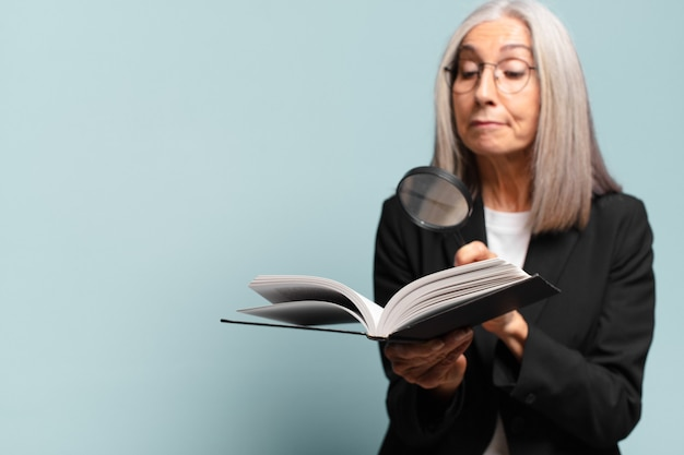 Starsza ładna kobieta z książką i lupą. koncepcja wyszukiwania