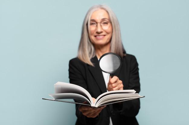 Starsza ładna kobieta z książką i lupą.