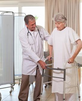 Starsza lekarka pomaga jego pacjentowi chodzić