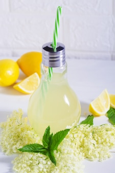 Starsza lemoniada zdrowy i orzeźwiający letni napój. zakończenie domowy syropu czarnego bzu up w butelce z starszymi kwiatami. letni napój napój szampański hugo z syropem z czarnego bzu, miętą i limonką.