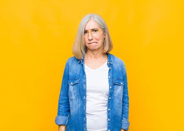 Starsza lub w średnim wieku kobieta wyglądająca na zaskoczoną i zdezorientowaną, przygryzająca wargę nerwowym gestem, nie znająca odpowiedzi na problem