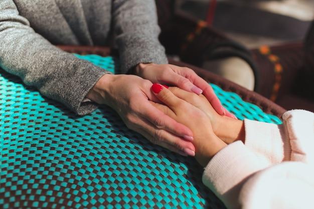 Starsza matka i jej młoda córka siedzą razem w kawiarni lub restauracji