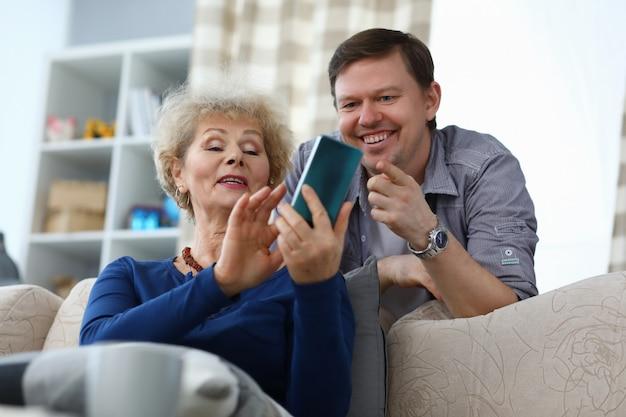 Starsza matka pokazuje zdjęcie dorosłemu synowi w telefonie