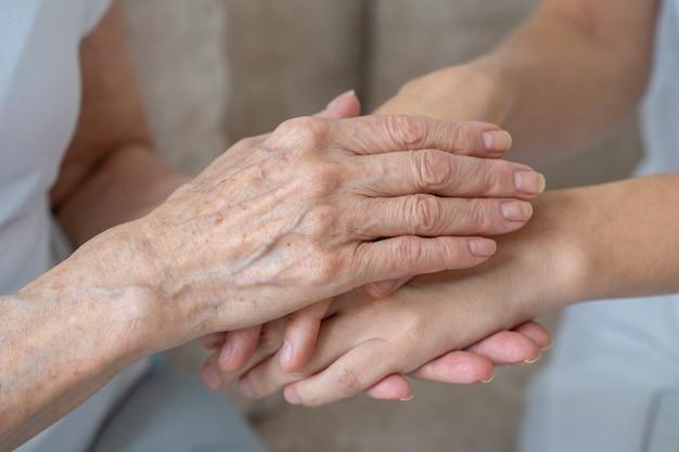 Starsza matka uspokaja córkę, głaszcze ją, trzyma ją za rękę w zbliżeniu