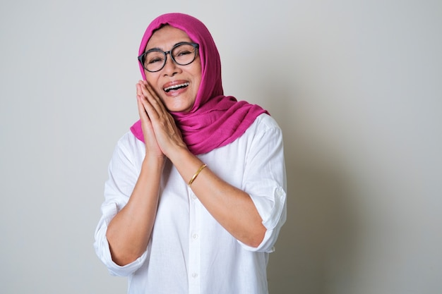 Starsza muzułmanka azjatka ubrana w hidżab pokazująca szczęśliwy wyraz twarzy