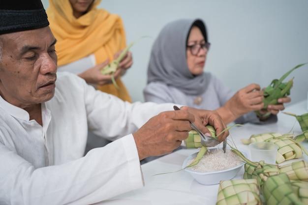 Starsza muzułmańska para i córka robią ketupat na uroczystość eid fitr mubarak w domu