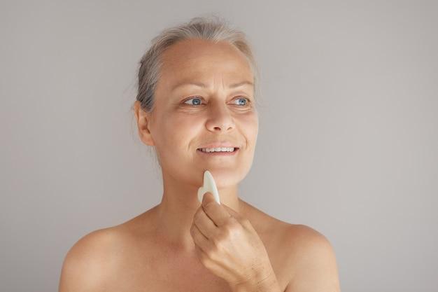 Starsza naga kobieta masuje twarz jadeitową deską odizolowaną na szarym tle