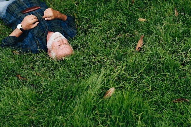 Starsza osoba mężczyzna dosypianie na zielonej trawie