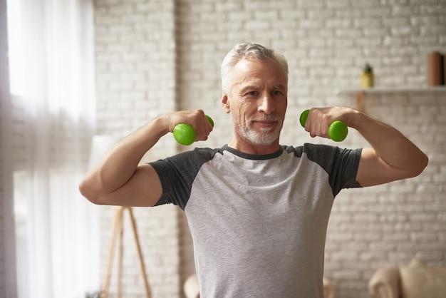 Starsza osoba mężczyzna trenuje bicep dumbbells ćwiczenia