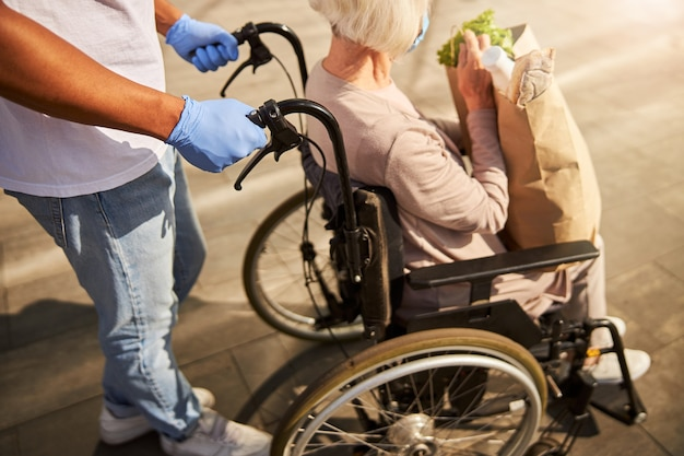 Starsza osoba niepełnosprawna z papierową torbą w ręku w drodze z centrum handlowego