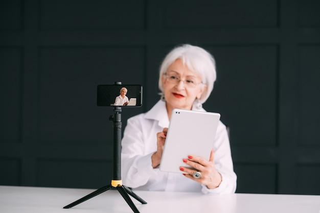 Starsza pani blogerka. trener biznesu online. stylowa starsza kobieta strumieniowego przesyłania wideo.