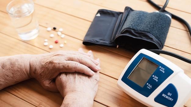 Starsza pani jest sprawdzana ciśnienie krwi za pomocą zestawu do pomiaru ciśnienia krwi