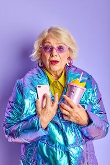 Starsza pani jest w szoku wiadomością lub podobną wiadomością, stoi przy smartfonie, odizolowana na fioletowym obszarze