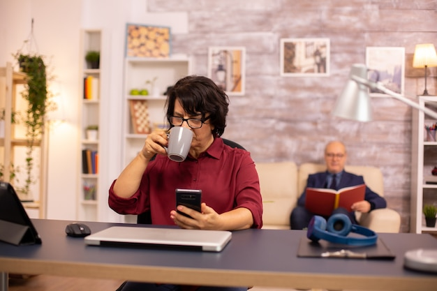 Starsza pani po sześćdziesiątce, korzystająca z nowoczesnej technologii w przytulnej przestrzeni mieszkalnej, podczas gdy jej mąż czyta w tle