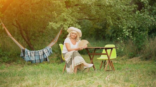 Starsza pani siedzi w ogrodzie