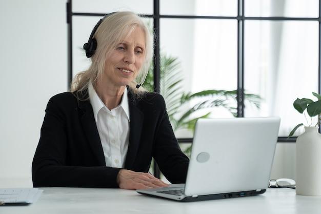 Starsza pani w słuchawkach rozmawia podczas wideokonferencji prowadzi wideokonferencję przy użyciu laptopa w biurze
