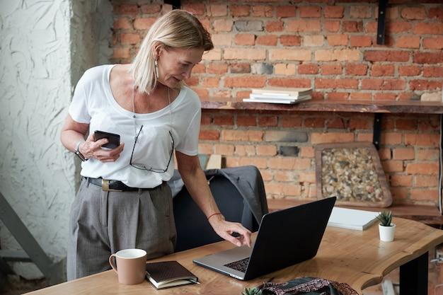 Starsza pani z okularami wiszącymi na szyi stojąc przy biurku i zapisując dokument online na laptopie