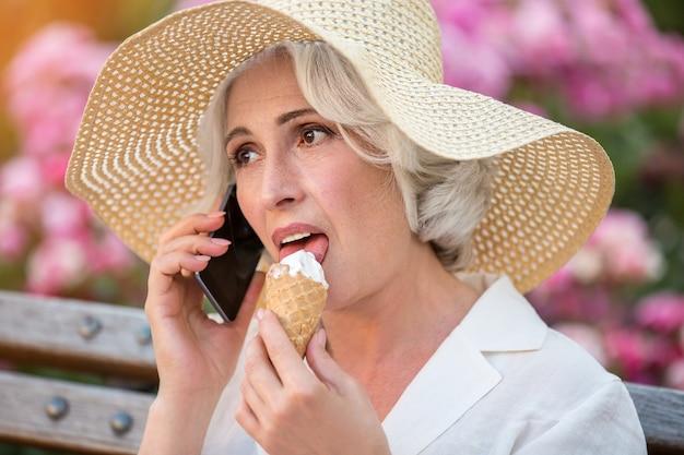 Starsza pani z telefonem komórkowym.