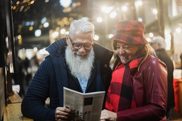 Starsza para bawi się na londyńskim rynku wieczorem - skup się na twarzach