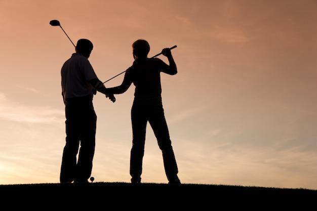 Starsza para bawić się golfa przy zmierzchem