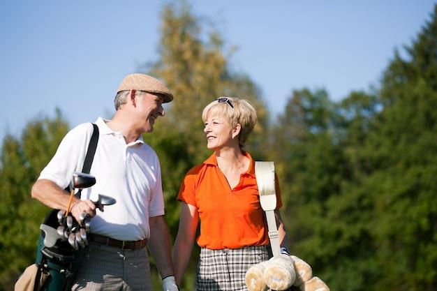 Starsza para bawić się golfa