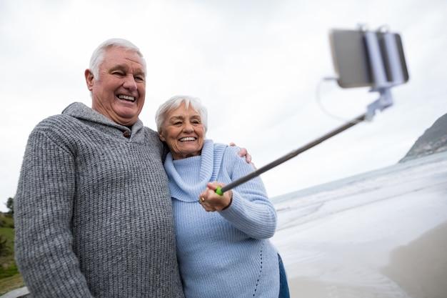 Starsza para bierze selfie od selfie kija
