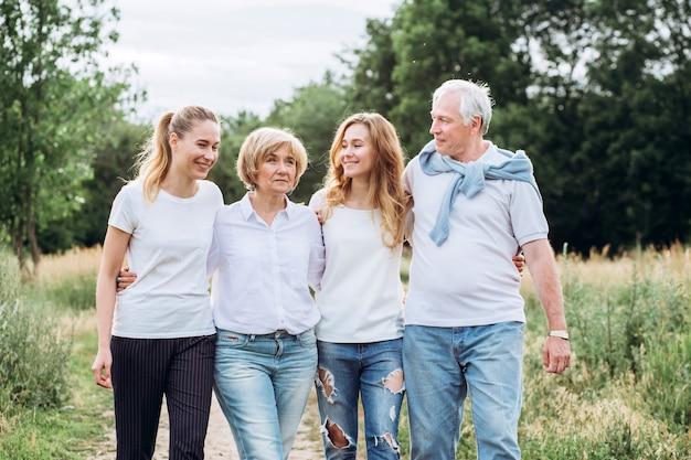 Starsza para chodzi z dorosłymi córkami w przyrodzie. starsza para spacery po lesie. w parku spaceruje rodzina w białych koszulkach i dżinsach. szczęśliwa rodzina. rodzina komunikuje się na zewnątrz