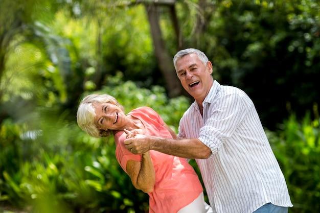 Starsza para cieszy się podczas gdy tanczący w jardzie