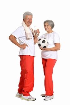 Starsza para ćwicząca z piłką i kciukami do góry na białym tle