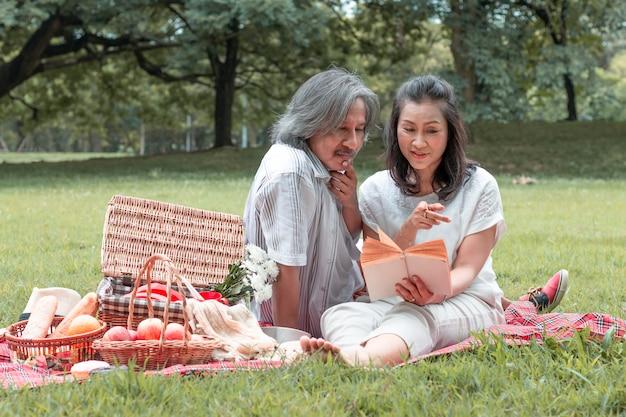 Starsza para czytanie książki i piknik w parku.