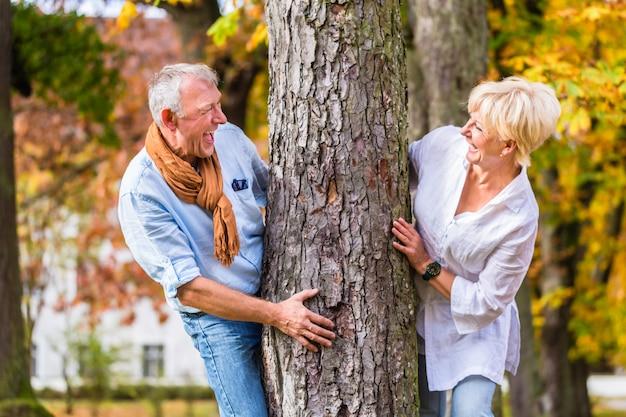Starsza para flirtuje bawić się wokoło drzewa w parku