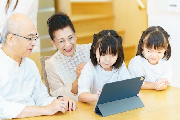 Starsza para i wnuki obsługują tablet pc na stole