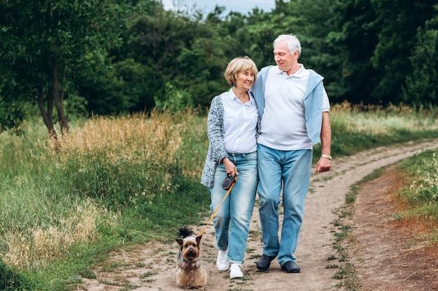 Starsza para idzie z psem w parku