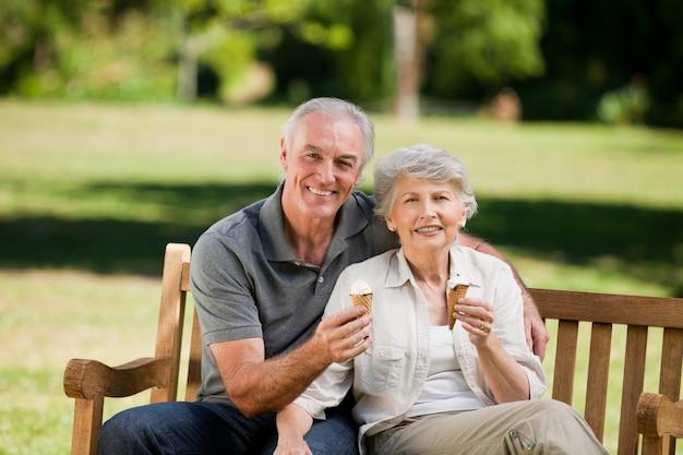 Starsza para je lody na ławce