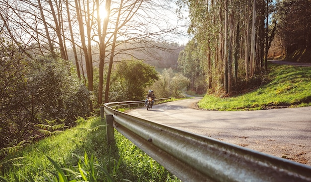 Starsza para jedzie na motocyklu po leśnej drodze jesienią