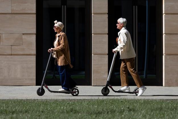Starsza para jedzie na skuterze elektrycznym po mieście