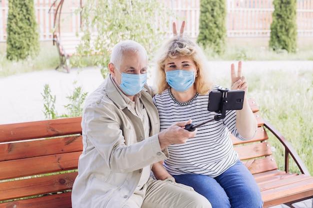 Starsza para jest ubranym medyczną maskę w celu ochrony przed koronawirusem i robi selfie w wiośnie lub letnim dniu