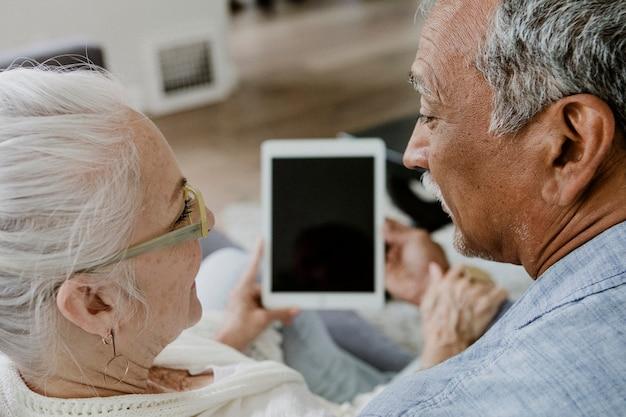 Starsza para korzysta z tabletu na kanapie