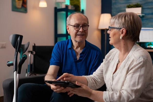 Starsza para korzystająca z nowoczesnego tabletu z internetem online
