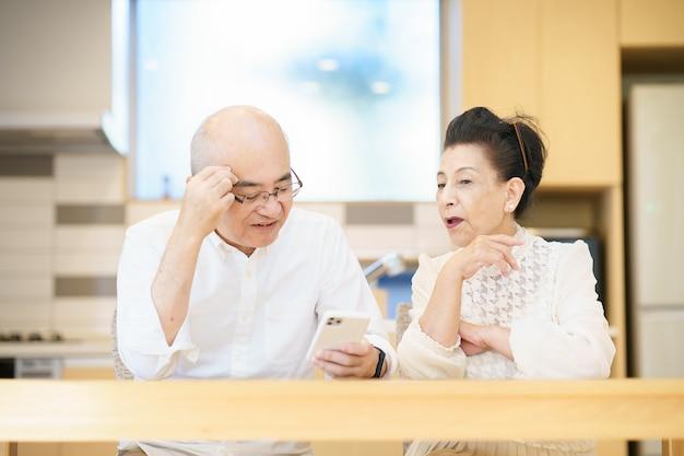Starsza para korzystająca ze smartfonów metodą prób i błędów w pokoju