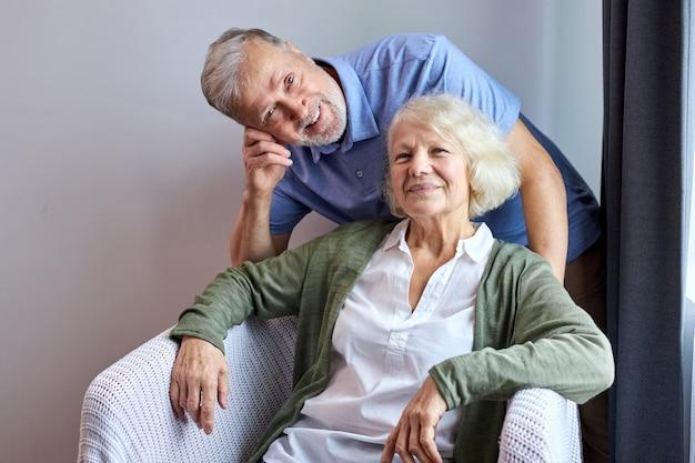Starsza para lat 60. relaksująca się w domu, pozująca uśmiechnięta chwila przechwytywania do rodzinnego albumu fotograficznego w domu, siwowłosy dziadkowie wieczna miłość