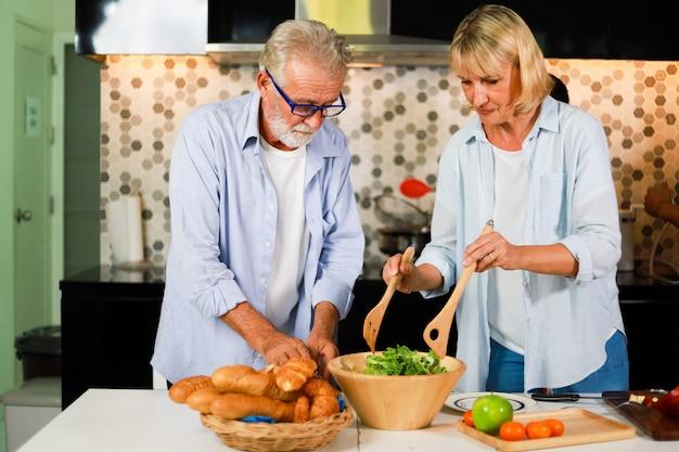 Starsza para mężczyzna i kobiety kucharstwo w kuchennym szczęśliwym nastroju
