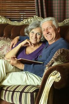 Starsza para na kanapie z książką