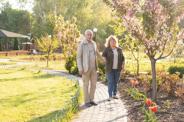 Starsza para na spacerze w wiośnie lub lato naturze