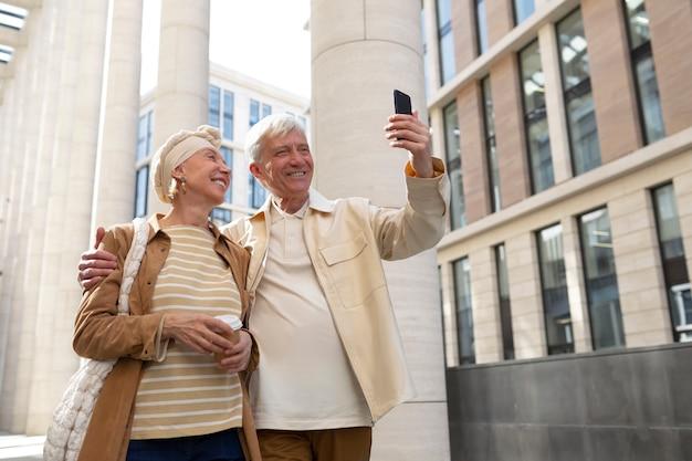 Starsza para na zewnątrz w mieście pije kawę i robi selfie