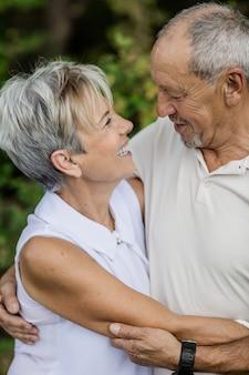Starsza para obejmująca się i wpatrująca się sobie w oczy zakochana, gdy spacerują po lesie na świeżym powietrzu.