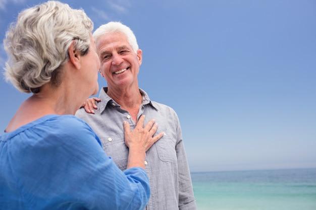 Starsza para obejmuje each inny na plaży