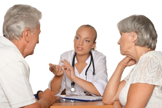 Starsza para odwiedzająca lekarkę na białym tle